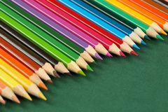Close up of many, bright multi colored wooden pencils in a row on a dark green background with copy space. Selective focus and sha stock images