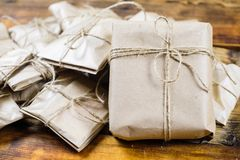Close-up many gifts wrapped kraft paper on wooden background. One big present front view royalty free stock photos