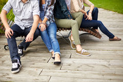 Close up of many legs sitting on bench at park Royalty Free Stock Image