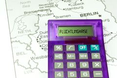 The map of Germany, a calculator and refugee crisis royalty free stock photos