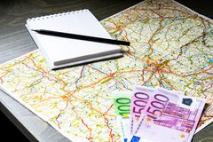 Close up of map, money, blank canvas notepad and pencil stock photo