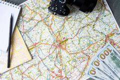 Close up of maps, money, camera, blank canvas notepad and pencil royalty free stock image