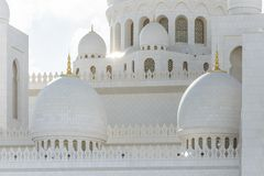 Close-up marble domes of Sheikh Zayed Grand Mosque with blue sky in the morning at Abu Dhabi, UAE stock photo