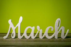 Close Up March word carved out of wood on green background. Spring beginning concept Stock Images