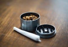 Close up of marijuana joint and herb grinder Royalty Free Stock Photos