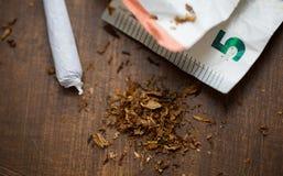Close up of marijuana joint and money. Substance abuse, nicotine addiction, drug sale and smoking concept - close up of marijuana joint and money Royalty Free Stock Image