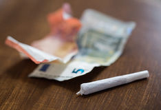 Close up of marijuana joint and money. Substance abuse, nicotine addiction, drug sale and smoking concept - close up of marijuana joint and money Royalty Free Stock Images