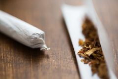 Close up of marijuana joint and tobacco. Drug use, substance abuse, nicotine addiction and smoking concept - close up of marijuana joint and tobacco Royalty Free Stock Images