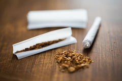 Close up of marijuana joint and tobacco. Drug use, substance abuse, nicotine addiction and smoking concept - close up of marijuana joint and tobacco Royalty Free Stock Photography