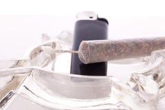 Close up of marijuana and smoking paraphernalia. Close up of marijuana joint made with translucent rolling papers, plastic baggy of dried marijuana, black Stock Image