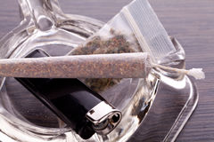 Close up of marijuana and smoking paraphernalia. Close up of marijuana joint made with translucent rolling papers, plastic baggy of dried marijuana, black Stock Images