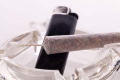 Close up of marijuana and smoking paraphernalia. Close up of marijuana joint made with translucent rolling papers, plastic baggy of dried marijuana, black Royalty Free Stock Photography