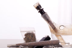 Close up of marijuana and smoking paraphernalia. Close up of marijuana joint made with translucent rolling papers, plastic baggy of dried marijuana, black Royalty Free Stock Photos