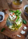 Close-up of marinated feta cheese in olive oil, herbs and red pepper flakes on wooden background stock images