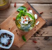 Close-up of marinated feta cheese in olive oil, herbs and red pepper flakes on wooden background, top view stock photo