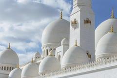Close-up marmeren koepels met gouden pijler met Islamitisch teken op de bovenkant van Sheikh Zayed Grand Mosque met blauwe hemel  Stock Foto's