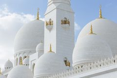 Close-up marmeren koepels met gouden pijler met Islamitisch teken op de bovenkant van Sheikh Zayed Grand Mosque met blauwe hemel  Stock Fotografie