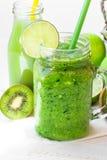 Close up mason jar mug with green fresh vegetable smoothie, bottle with fruit juice, lime slice, kiwi, apples, outdoors Royalty Free Stock Image