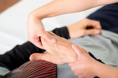 Close up of a massage physiotherapist doing hand massage of a male athlete, in medical office background Stock Photography