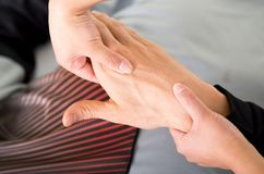Close up of a massage physiotherapist doing hand massage of a male athlete, in medical office background Royalty Free Stock Images