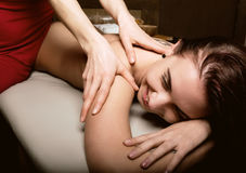 Close-up masseur hands doing spin massage, relaxed patient enjoys Royalty Free Stock Photo