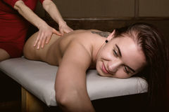 Close-up masseur hands doing spin massage, relaxed patient enjoys Stock Photos