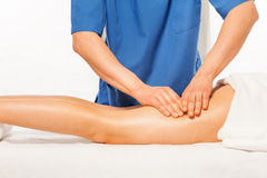Close-up of masseur's hands kneading female hip Royalty Free Stock Photo