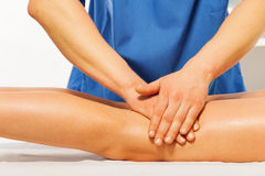 Close-up of masseur's hands kneading female leg Royalty Free Stock Image