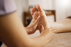 Masseuse massaging female foot at the spa royalty free stock photography