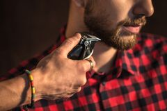 Close-up of Master cuts hair and beard of men. In the barbershop, hairdresser makes hairstyle for a young man Royalty Free Stock Photo