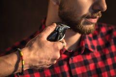 Close-up of Master cuts hair and beard of men Royalty Free Stock Photo