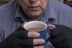 Mature Caucasian man clutching a hot drink royalty free stock photo