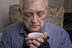 Mature Caucasian man clutching a hot drink stock photography