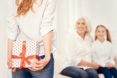 Close up of mature lady holding gift box behind back royalty free stock photography
