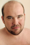 Close up mature man. Detailed closeup portrait of a mature balding man with beard against warm neutral background Royalty Free Stock Photo