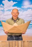 Close up of mature man with brown paper origami boat, concept for aspirations, leadership, strategy or just boredom in. The office, in a beach background stock photos