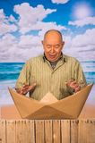 Close up of mature man with brown paper origami boat, concept for aspirations, leadership, strategy or just boredom in. The office, in a beach background stock image