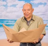 Close up of mature man with brown paper origami boat, concept for aspirations, leadership, strategy or just boredom in. The office, in a beach background royalty free stock photography