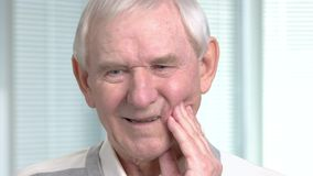 Close up mature man having toothache. Unhappy senior man touching his cheek outside and suffering from teeth pain, blurred background stock video