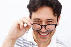 Mature man holding glasses and smiling Stock Photo