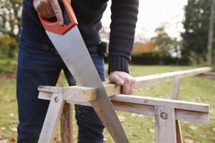 Close Up Of Mature Man Sawing Wood Outdoors Stock Image