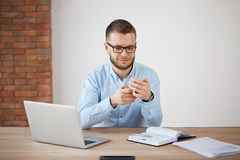 Close up of mature unshaven man in glasses and shirt at work, chatting with wife by smartphone during lunch. Manager. Sitting in office, making research using Royalty Free Stock Photo