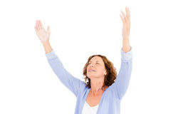 Close-up of mature woman with arms raised while praying. Against white background royalty free stock photos