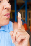 Close up mature Woman blowing band aid finger Royalty Free Stock Photos