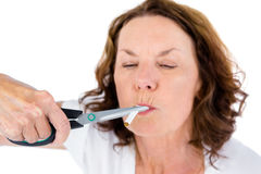 Close-up of mature woman cutting cigarette with scissors. Against white background Stock Photo