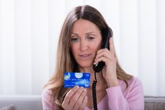 Woman Holding Credit Card While Talking On Telephone royalty free stock photos