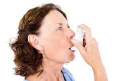 Close-up of mature woman using asthma inhaler. Against white background stock image
