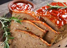 Close-up of a meatloaf on board. Close-up of delicious meatloaf cut in slices on cutting board  with garlic, rosemary, and tomato sauce, horizontal view from Stock Photography
