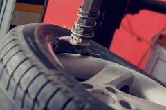 Mechanic balancing car wheel on balancer. Close up of mechanic balancing car wheel on balancer royalty free stock photography