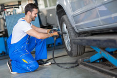 Close up of mechanic changing wheel Stock Images